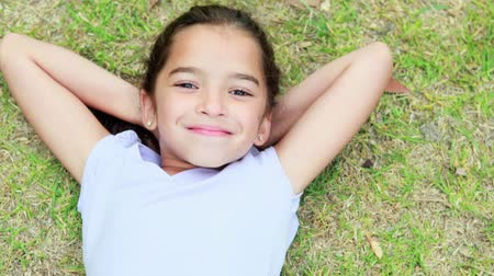 girl : Happy little girl lying on grass and looking at camera in park Stock Footage