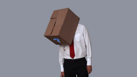 noktalama : Businessman looking down with box on head on grey background
