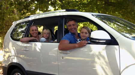 otopark : Happy family getting ready for road trip and looking at camera on sunny day