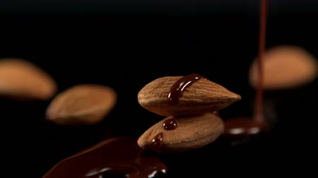 mandula : Melted chocolate pouring over almonds in slow motion