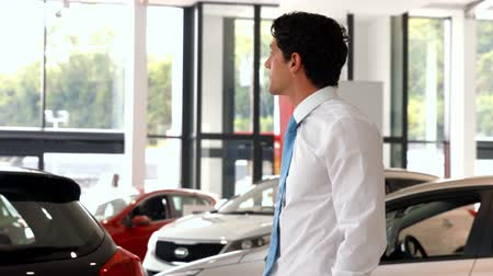 krawat : Businessman looking at the selection of cars at the car showroom