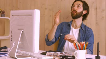 throwing in : Hipster worker throwing ball at desk in creative office