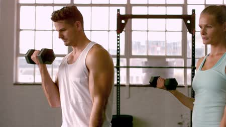 levantamento de pesos : Fit people lifting dumbbells in gym in slow motion