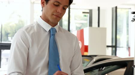 krawat : Man in a suit signing a document at the car showroom Wideo