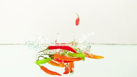 biber : Chili peppers falling in water in slow motion