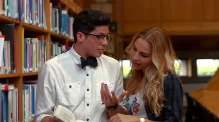 bochecha : Pretty student talking to nerd in library at the college Stock Footage