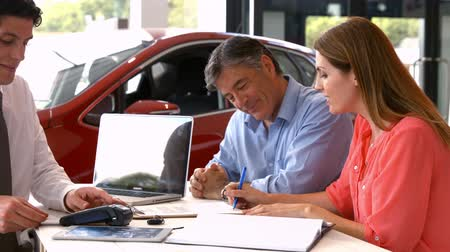 sala de exposição : Customers sigining some important documents at the car showroom