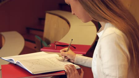aluno : Student taking down notes in class in the university college Stock Footage