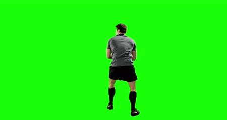 komoly : Rear view of serious rugby player on green background Stock mozgókép