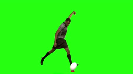 jogador : Serious rugby player kicking ball on green screen background