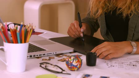 grafika : Graphic designer using digitizer at her desk in creative office Wideo