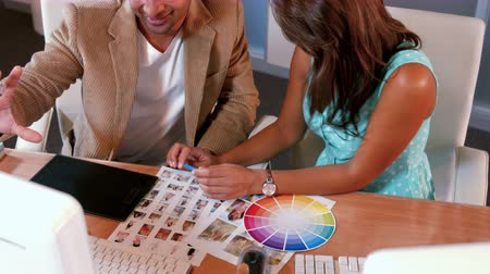 ügynökség : Casual designer looking at photo sample and color sample in office Stock mozgókép