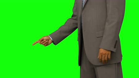 tenso : Close up of businessman pointing with his finger on green screen background