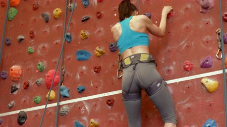 wspinaczka : Woman climbing up rock wall in high quality 4k format Wideo