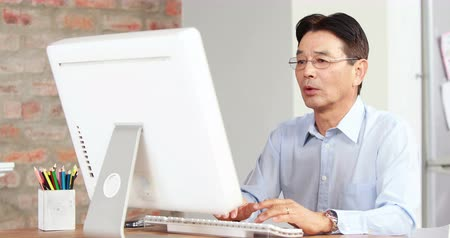 apprehensive : Asian businessman using computer at desk in high quality 4k format Stock Footage
