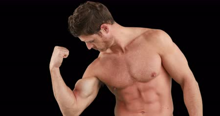 kaslı : Muscular man flexing his muscles on black background Stok Video