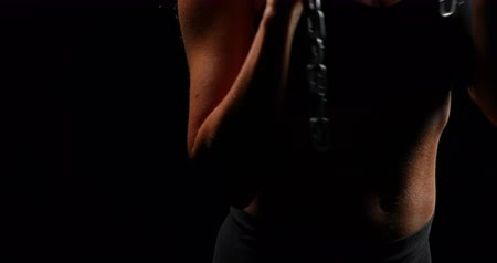 gritar : Aggressive muscular woman holding chain against black background