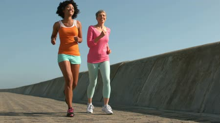 kimerül : Two fit women running together outside Stock mozgókép