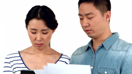 sufferance : Young unsmiling couple doing their account against white background