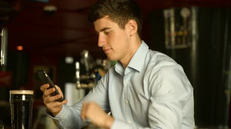 паб : Man using phone at the bar in high quality  Стоковые видеозаписи