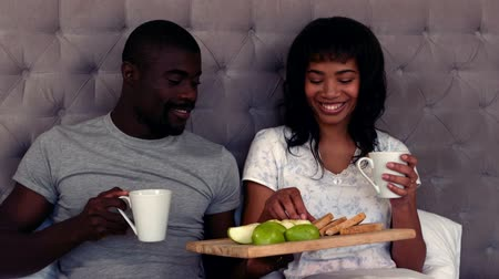 daireler : Smiling couple taking breakfast on bed at home