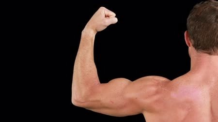 bicep : Bodybuilder posing for the camera on black background