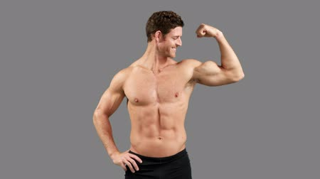 fisiculturismo : Muscular man with thumbs up posing on grey background