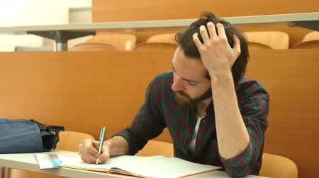 confuso : Stressed student taking down notes in class