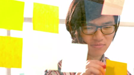 írás : Happy hipster writing on sticky note in slow motion Stock mozgókép