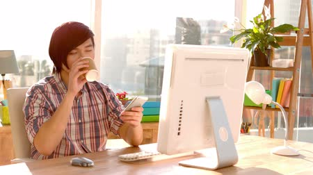 coffee time : Handsome hipster having coffee and using smartphone in his office