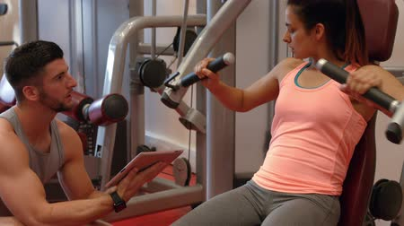 eğitici : Trainer motivating client using weight machine in ultra hd format Stok Video