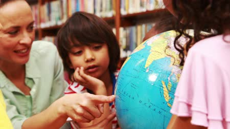 könyvtár : Pupils and teacher looking at globe in library in high quality
