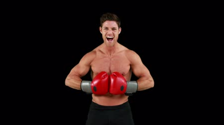 fisiculturismo : Shirtless angry boxer with gloves against black background