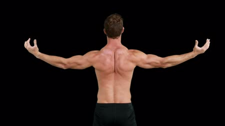 confiança : Rear view  of muscular man outstretching his arms on black background Vídeos