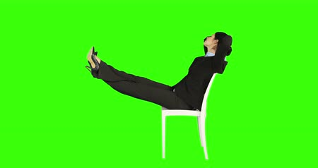 ül : Business woman relaxing on a chair with legs up on green screen Stock mozgókép