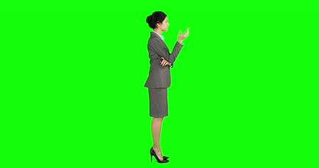 стоять : Businesswoman standing under umbrella on green screen