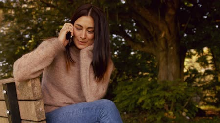 serene : Pretty brunette using phone in park in high quality format Stock Footage