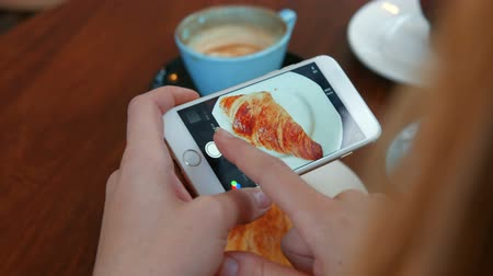 fotografando : Woman photographing her croissant on smartphone in high quality format Vídeos