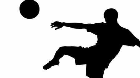 futbol topu : Silhouette of soccer player kicking ball on white screen
