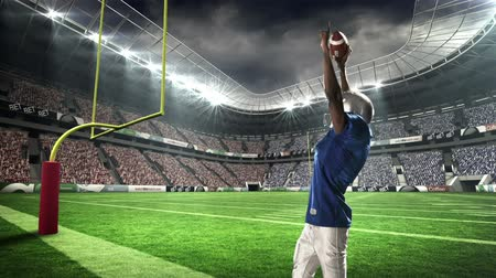 atleta : American football player triumphing with raised arms at stadium