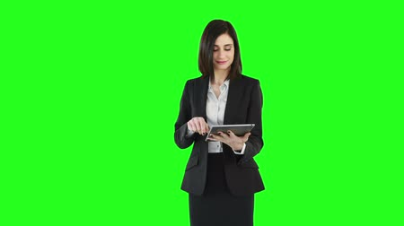 kobiety : Business woman standing and using a tablet on green screen Wideo
