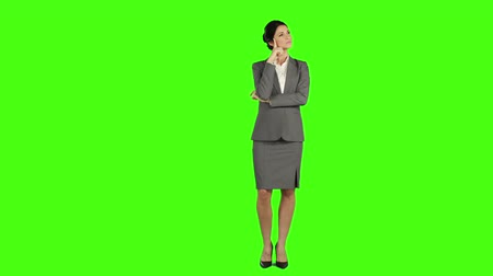 стоять : Thoughtful business woman standing and smiling at the camera on green screen
