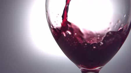 bordo : Red wine pouring into wine glass in slow motion