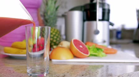 diety : Woman pouring fresh fruit and vegetable juice at home in the kitchen