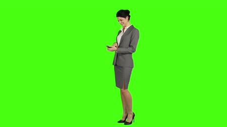смеющийся : Business woman laughing while using a smartphone and looking at the camera on green screen