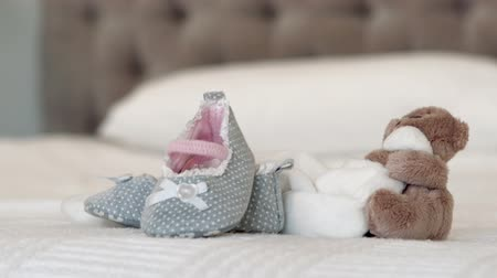 booties : Baby shoes and teddy bear on bed at home