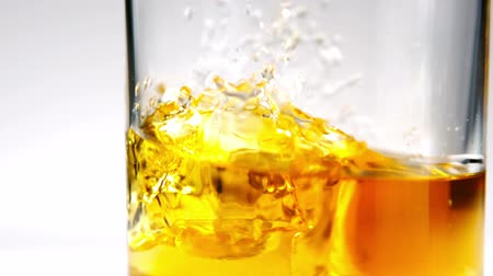 whisky : Close up view of ice falling into tumbler of whiskey and ice