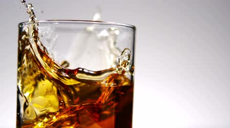 viski : Close up view of ice falling into tumbler of whiskey and ice