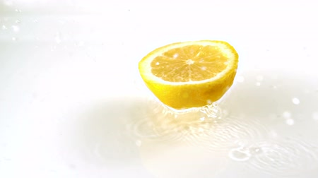 cytryna : Close up view of lemon slices falling into water