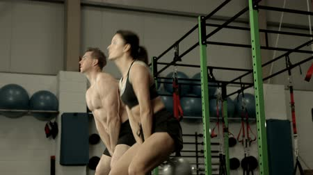 swing : Fit couple squatting with kettlebells in crossfit gym